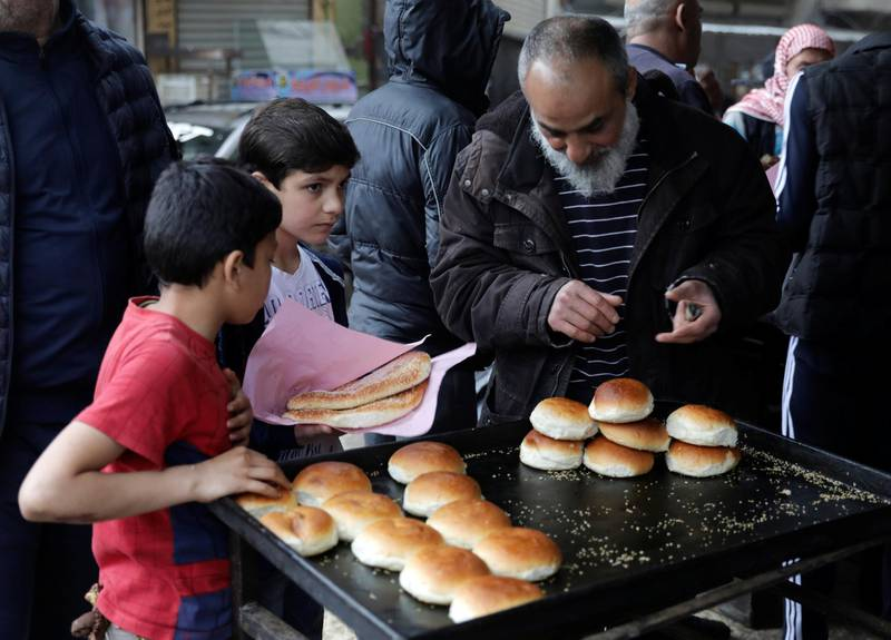 People buy traditional bread at a bakery before the time for iftar, or breaking fast, on the first day of the holy month of Ramadan, as the spread of the coronavirus disease (COVID-19) continues, in the rebel-held Idlib city, Syria April 24, 2020. REUTERS/Khalil Ashawi