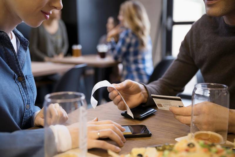 Close up couple with credit card paying bill calculating tip with smart phone in brewery restaurant. Getty Images