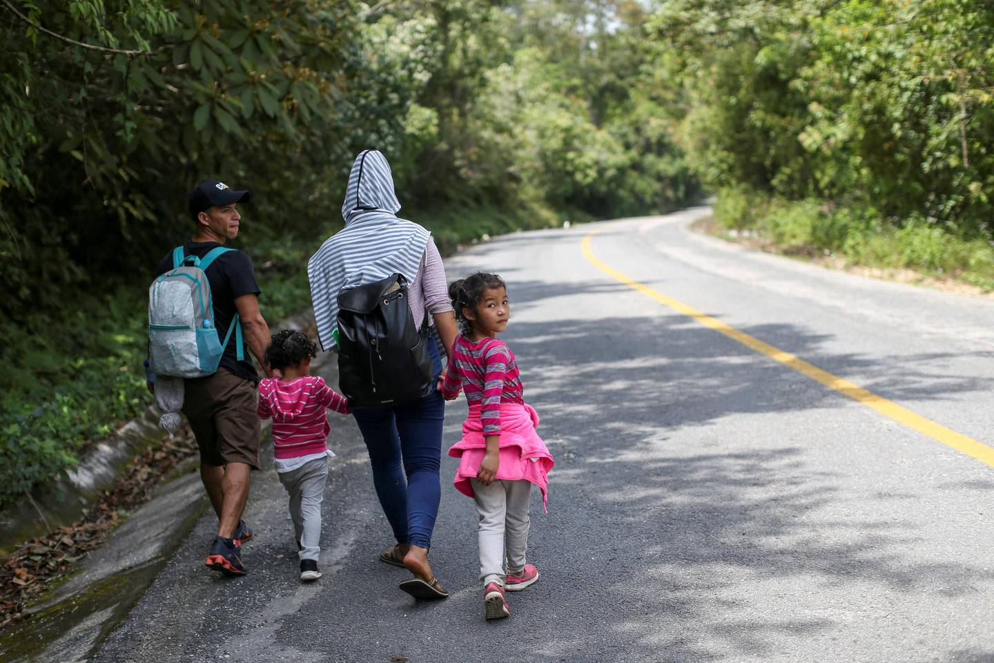 A Honduran migrant family trying to reach the U.S. walks on a highway on the outskirts of Palenque, Mexico March 8, 2021. Picture taken March 8, 2021. REUTERS/Edgard Garrido