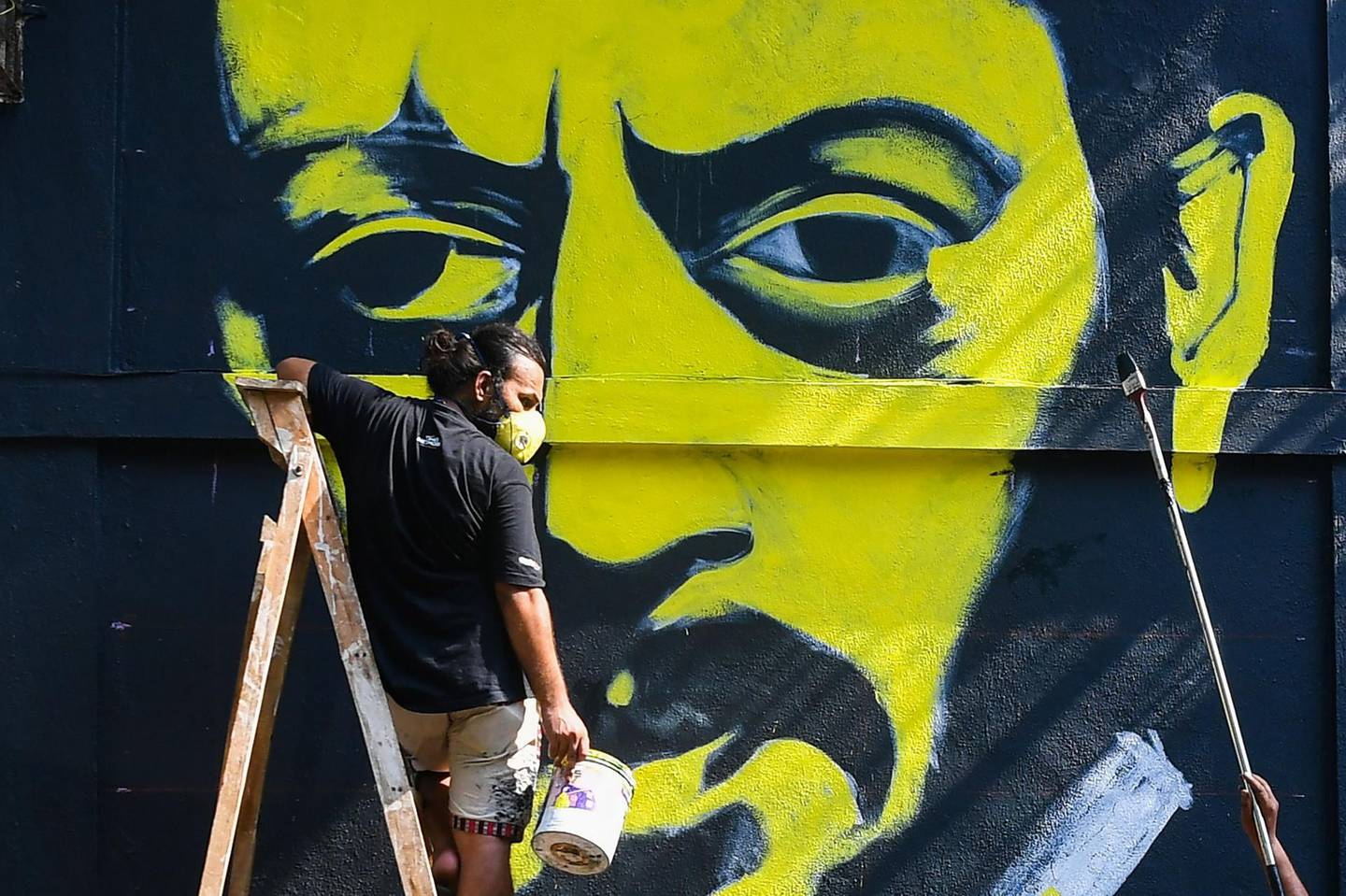 """Artists work on a mural of late Bollywood actor Irrfan Khan on a wall in a neighbourhood in Mumbai on May 1, 2020. Acclaimed Indian actor Irrfan Khan, whose international movie career included hits such as """"Slumdog Millionaire"""", """"Life of Pi"""" and """"The Amazing Spider-Man"""", died at the age of 53 on April 29. / AFP / Indranil MUKHERJEE"""