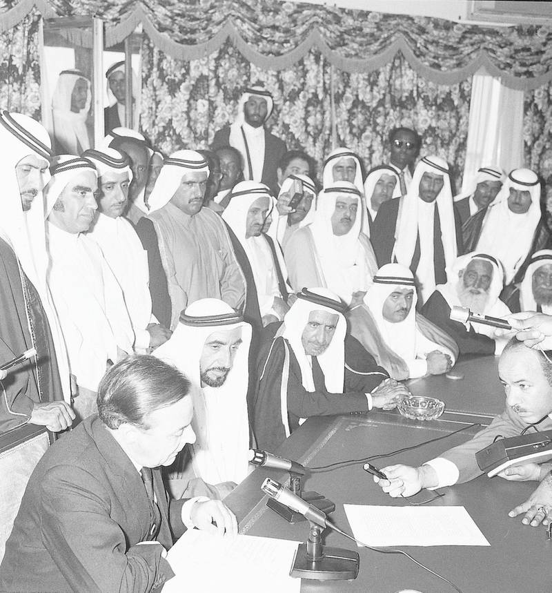 1971. President Shaikh Zayed Bin Sultan Al Nahyan with the other rulers of the emirates, government representatives and media listen to the British political agent as he reads the document proclaiming the federation and the UAE's independence. - WAM