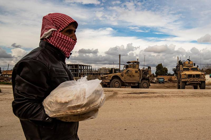 A man carrying bags of bread walks as a patrol of US military vehicles is seen in the town of Tal Tamr in the northeastern Syrian Hasakeh province along the border with Turkey on February 8, 2020. (Photo by Delil SOULEIMAN / AFP)