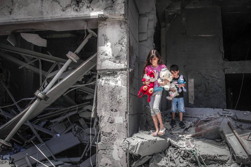 TOPSHOT - Palestinian children salvage toys from their home at the Al-Jawhara Tower in Gaza City, on May 17, 2021, which was heavily damaged in Israeli airstrikes. / AFP / ANAS BABA