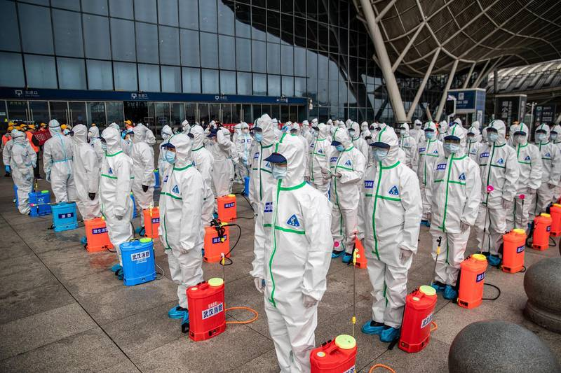 TOPSHOT - Staff members line up at attention as they prepare to spray disinfectant at Wuhan Railway Station in Wuhan in China's central Hubei province on March 24, 2020. - China announced on March 24 that a lockdown would be lifted on more than 50 million people in central Hubei province where the COVID-19 coronavirus first emerged late last year. (Photo by STR / AFP) / China OUT (Photo by STR/AFP via Getty Images)