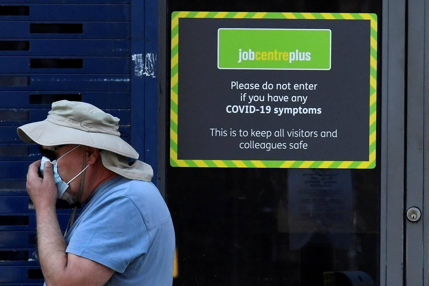 FILE PHOTO: A person wearing a protective face mask walks past a Job Centre Plus office, amidst the outbreak of the coronavirus disease (COVID-19) in London, Britain, August 11, 2020. REUTERS/Toby Melville/File Photo