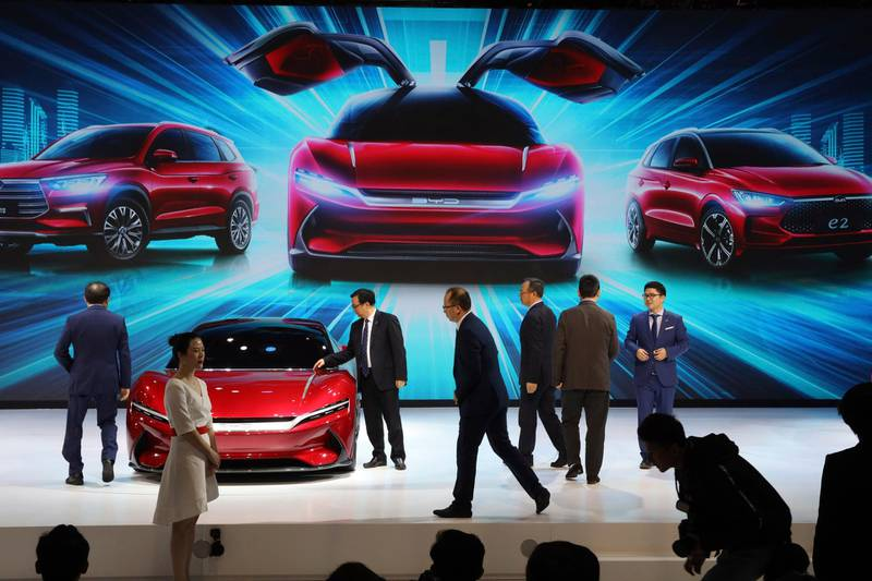 FILE - In this April 16, 2019, file photo, attendees take a close look at cars from BYD at the Auto Shanghai 2019 show in Shanghai. China's auto sales plunged 81.7% in February, 2020,  from a year ago after Beijing shut down much of the economy to fight a virus outbreak, adding to problems for an industry that already was struggling with shrinking demand. (AP Photo/Ng Han Guan, File)