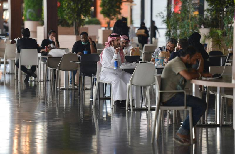 People sit at a cafe in a mall in the Saudi capital Riyadh on June 4, 2020, after it reopened following the easing of some restrictions put in place by the authorities in a bid to stem the spead of the novel coronavirus. (Photo by FAYEZ NURELDINE / AFP)