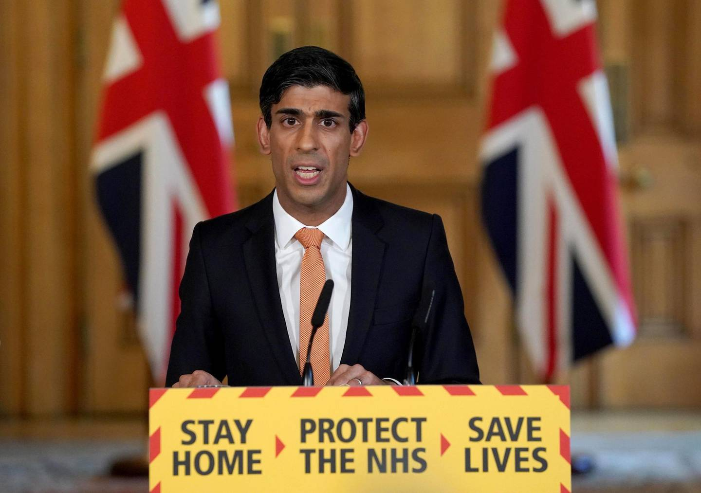 """A handout image released by 10 Downing Street, shows Britain's Chancellor of the Exchequer Rishi Sunak speaking during a remote press conference to update the nation on the COVID-19 pandemic, inside 10 Downing Street in central London on April 8, 2020. Britain's Prime Minister Boris Johnson was """"responding to treatment"""", his spokesman said Wednesday, as the 55-year-old leader spent a third day in intensive care battling the coronavirus.  - RESTRICTED TO EDITORIAL USE - MANDATORY CREDIT """"AFP PHOTO / 10 DOWNING STREET / PIPPA FOWLES"""" - NO MARKETING - NO ADVERTISING CAMPAIGNS - DISTRIBUTED AS A SERVICE TO CLIENTS  / AFP / 10 Downing Street / Pippa FOWLES / RESTRICTED TO EDITORIAL USE - MANDATORY CREDIT """"AFP PHOTO / 10 DOWNING STREET / PIPPA FOWLES"""" - NO MARKETING - NO ADVERTISING CAMPAIGNS - DISTRIBUTED AS A SERVICE TO CLIENTS"""