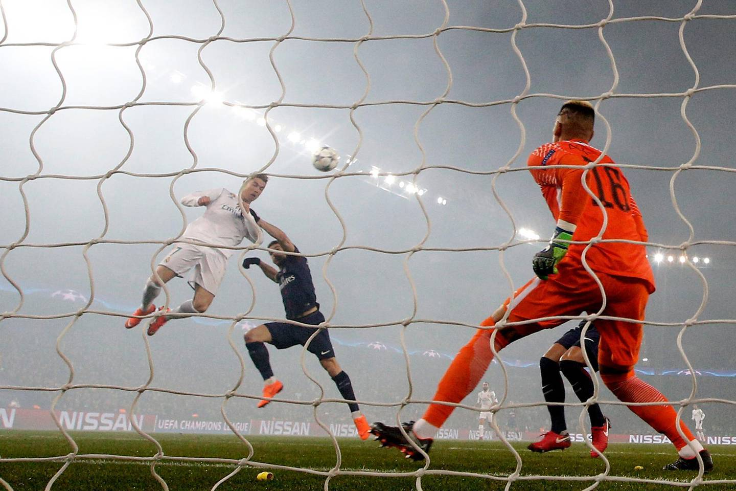 Real Madrid's Cristiano Ronaldo heads the ball to score his side's first goal passing PSG goalkeeper Alphonse Areola during the Champions League round of sixteen second leg soccer match between Paris St. Germain and Real Madrid at the Parc des Princes stadium in Paris, France, Tuesday, March 6, 2018. (AP Photo/Christophe Ena)