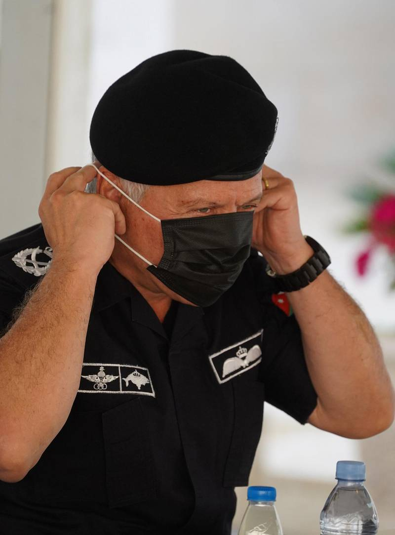 """A handout picture released by the Jordanian Royal Palace on November 17, 2020 shows Jordanian King Abdullah II, who is the Supreme Commander of the armed forces, putting on a mask as a protective measure against the coronavirus pandemic, while addressing policemen at the Public Security Directorate in Amman.    - RESTRICTED TO EDITORIAL USE - MANDATORY CREDIT """"AFP PHOTO / JORDANIAN ROYAL PALACE / YOUSEF ALLAN"""" - NO MARKETING NO ADVERTISING CAMPAIGNS - DISTRIBUTED AS A SERVICE TO CLIENTS  / AFP / Jordanian Royal Palace / Yousef ALLAN / RESTRICTED TO EDITORIAL USE - MANDATORY CREDIT """"AFP PHOTO / JORDANIAN ROYAL PALACE / YOUSEF ALLAN"""" - NO MARKETING NO ADVERTISING CAMPAIGNS - DISTRIBUTED AS A SERVICE TO CLIENTS"""