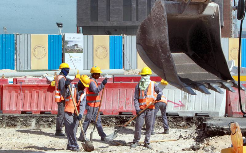 """Workers are seen at a construction site in Doha, on November 16, 2014. Qatar, host of the 2022 football World Cup, pledged  to introduce new legislation to replace the controversial """"kafala"""" sponsorship system and improve conditions for migrant workers by early 2015. The current law, which limits the rights of movement for foreign workers, would make way for legislation that was """"currently under review,"""" said the labour and social affairs ministry.  AFP PHOTO/STR / AFP PHOTO / -"""
