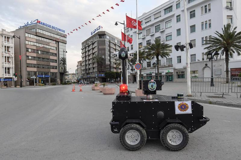 A Tunisian police robot patrols along Avenue Habib Bourguiba in the centre of the capital Tunis on April 1, 2020, as a means of enforcing a nationwide lockdown to combat the COVID-19 coronavirus pandemic. The locally-built robots are remotely operated and equipped with infrared and thermal imaging cameras, in addition to a sound and light alarm system. / AFP / FETHI BELAID