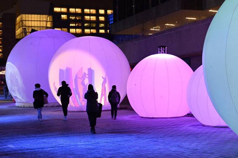 """People enjoy the 'New Moon' sound-and-light installation, consisting of seven inflated spheres that reveal through shadows and light, iconic images and stories inspired by the culture of the Quartier des Spectacles, on December 14, 2020 in Montreal, Quebec,  one of the five light installations on display to bring some comfort to residents of a city that has been battered by months of coronavirus. - In the heart of downtown Montreal, a special sound and light display has been set up to try to bring some comfort to residents of a city that has been battered by months of coronavirus, and may be in need of a little seasonal """"light therapy"""". Sitting inside one of these 19th-century pre-cinematic contraptions, Alison Abrego and Salma Houaichi, both 27, push a lever towards each other that rolls the illustrations on the cylinder, giving the impression that the images are coming to life. (Photo by Eric THOMAS / AFP)"""