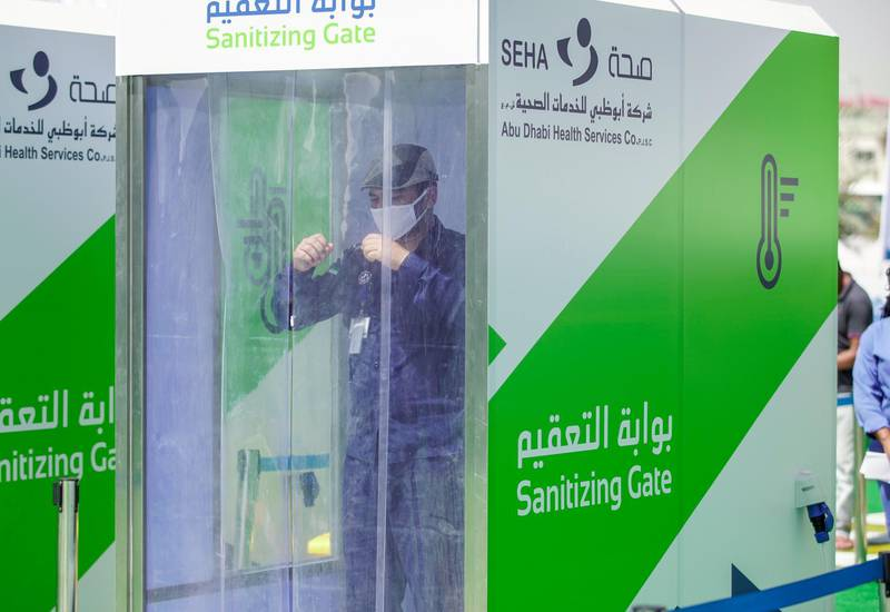 Abu Dhabi, United Arab Emirates, May 6, 2020. the new Ambulatory Healthcare Services, a SEHA Health System Facility, National Screening Project in Mussafah Industrial Area in Abu Dhabi.   -- A worker enters the Sanitising Gate before before entering the main tent screening center.Victor Besa / The NationalSection:  NAReporter:  Nick Webster