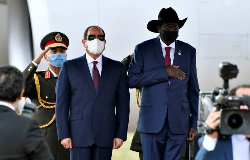 Egypt's President Abdel Fattah al-Sisi and South Sudan's President Salva Kiir, wearing protective face masks, stand as they listen to national anthems in Juba, South Sudan, November 28, 2020. REUTERS/Jok Solomun