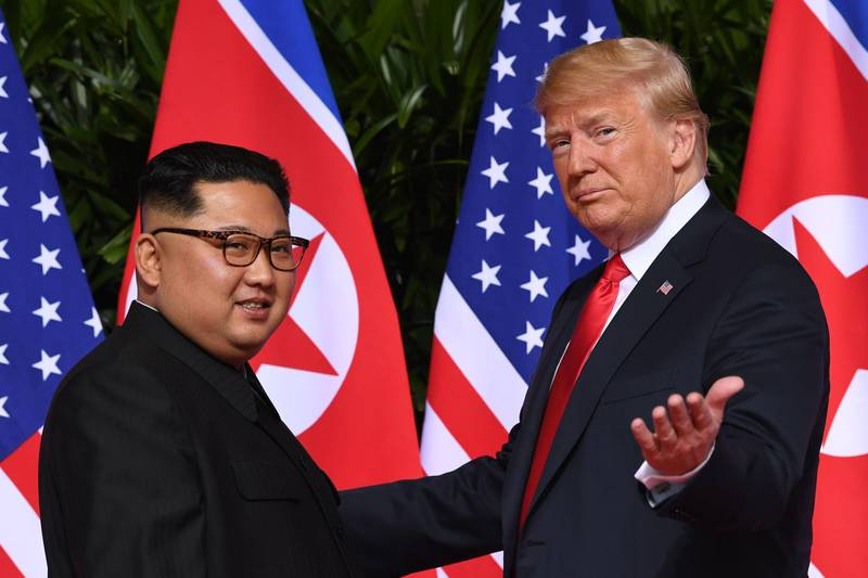 -- AFP PICTURES OF THE YEAR 2018 --  US President Donald Trump (R) gestures as he meets with North Korea's leader Kim Jong Un (L) at the start of their historic US-North Korea summit, at the Capella Hotel on Sentosa island in Singapore on June 12, 2018. Donald Trump and Kim Jong Un have become on June 12 the first sitting US and North Korean leaders to meet, shake hands and negotiate to end a decades-old nuclear stand-off. -   / AFP / SAUL LOEB