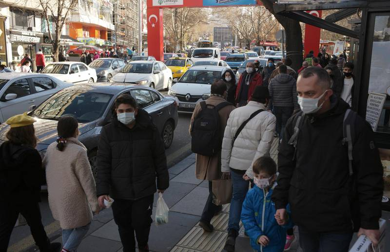 People wearing masks to help protect against the spread of coronavirus, walk along a busy shopping street, in Ankara, Turkey, Wednesday, Dec. 30, 2020. A first batch of vaccines developed by Chinese biopharmaceutical company Sinovac have arrived in Turkey, after a two-week delay. A plane carrying 3 million doses of the CoronaVac vaccine landed in the capital Ankara early on Wednesday.(AP Photo/Burhan Ozbilici)