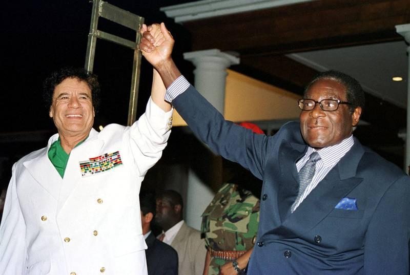 FILE PHOTO: Libyan leader Colonel Muammar Gaddafi (L) and Zimbabwe President Robert Mugabe greet supporters outside State House in Harare, Zimbabwe July 12, 2001. REUTERS/Stringer/File Photo