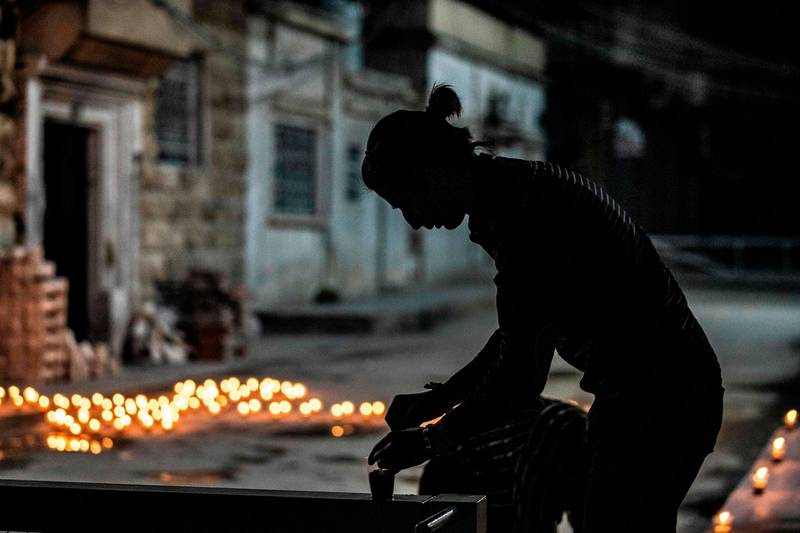 A worshipper lights a candle outside the closed Syriac Orthodox Church of the Virgin Mary as he marks Palm Sunday amid the coronavirus (COVID-19) pandemic in the northeastern Syrian Kurdish-controlled city of Qamishli, on April 12, 2020.  / AFP / DELIL SOULEIMAN
