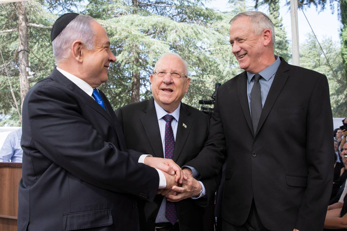 epa08373681 (FILE) -  Israeli Prime Minister Benjamin Netanyahu (L), Israeli President Reuven Rivlin (C) and Benny Gantz, former Israeli Army Chief of Staff and chairman of the Blue and White Israeli centrist political alliance (R) join hands as they attend a memorial service for late Israeli president Shimon Peres at Mount Herzl in Jerusalem, 19 September 2019(issued 04 April 2020). Media report that Netanyahu  and Gantz agreed to sign a coalition deal to form a government after three elections and to rotate the premiership.  EPA/ABIR SULTAN