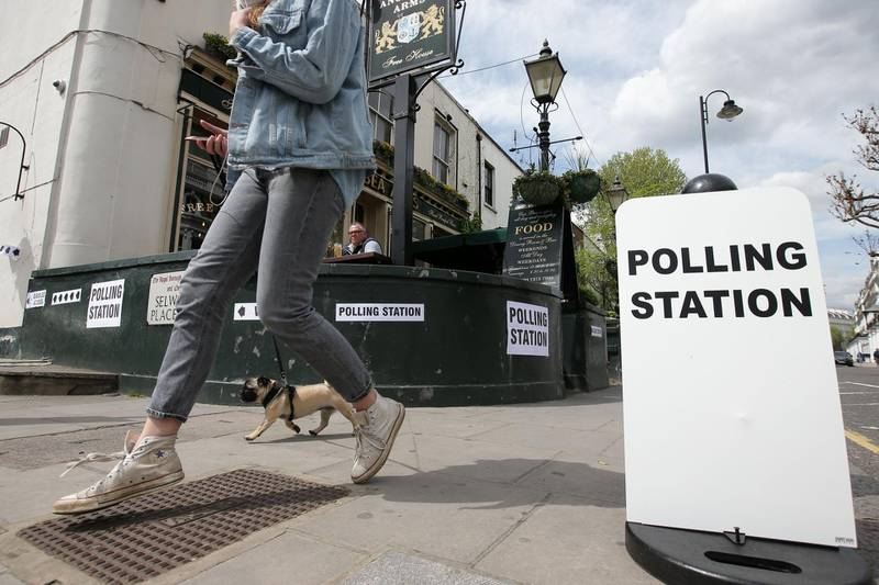 People enjoy a lunchtime drink in the sunshine outside the Anglesea Arms, which is acting as a polling station in the Borough of Kensington and Chelsea in London on May 3, 2018, as local council elections take place across the capital. Voters in England went to the polls Thursday to choose local councillors in the first electoral test for Prime Minister Theresa May since she lost her parliamentary majority last year. / AFP PHOTO / Daniel LEAL-OLIVAS