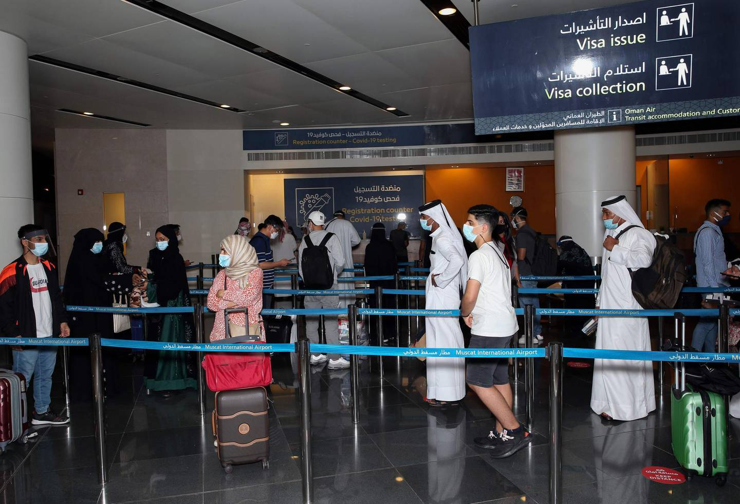 Passengers, wearing protective face mask due to the Covid-19 pandemic, stand in a queue at the Muscat international airport in the Omani capital on October 1, 2020.  / AFP / MOHAMMED MAHJOUB