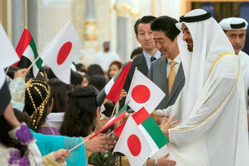 ABU DHABI, UNITED ARAB EMIRATES - January 13, 2020: School children welcome HH Sheikh Mohamed bin Zayed Al Nahyan, Crown Prince of Abu Dhabi and Deputy Supreme Commander of the UAE Armed Forces (R) and HE Shinzo Abe, Prime Minister of Japan (2nd R), during a reception, at Qasr Al Watan.  ( Hamad Al Kaabi / Ministry of Presidential Affairs ) ---
