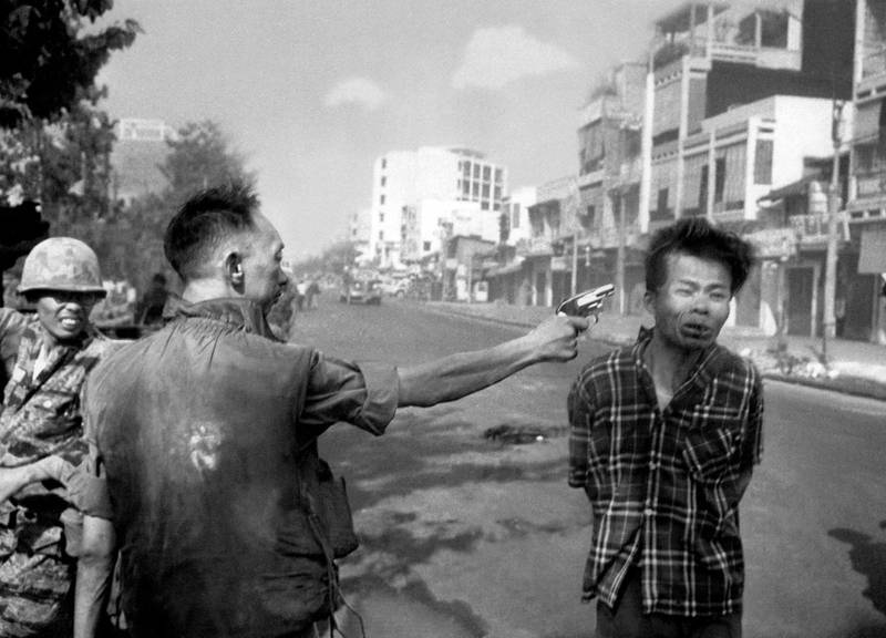 """FILE - In this Feb. 1, 1968, file photo, South Vietnamese Gen. Nguyen Ngoc Loan, chief of the National Police, fires his pistol into the head of suspected Viet Cong officer Nguyen Van Lem (also known as Bay Lop) on a Saigon street, early in the Tet Offensive. """"Vietnam: The Real War,"""" a collection of 58 photographs taken by the AP opens to the public Friday, June 12, 2015, in Hanoi, (AP Photo/Eddie Adams, File)"""
