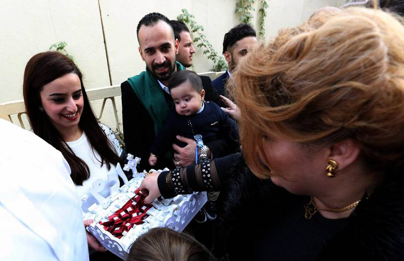 epa06405419 An Iraqi Christian woman distributes sweets after a Christmas mass at a Church in Baghdad's Karada district, Iraq, 25 December 2017. Christians in Iraq celebrated Christmas as Iraqi forces impose security measures against terrorist attacks around the churchs in the country. About a million Iraqi Christians have either left the country or have been killed since 2003.  EPA/ALI ABBAS
