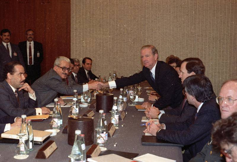 U.S. Secretary of State James Baker (5th R) and Iraqi Foreign Minister Tariq Aziz shake hands at the request of photographers at the start of their meeting in Geneva January 9, 1991.    REUTERS/Landov   QUALITY FROM SOURCE