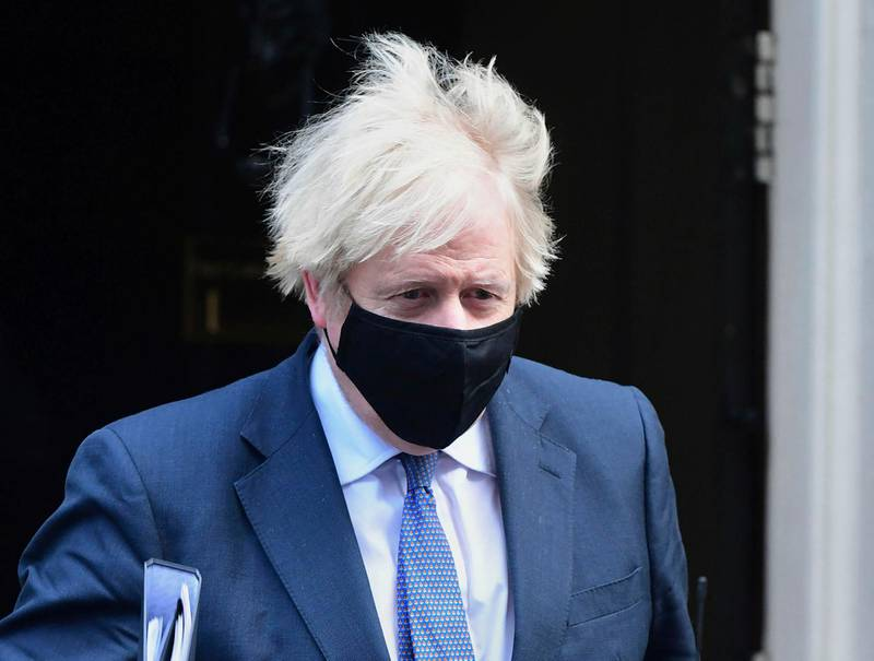 Britain's Prime Minister Boris Johnson leaves 10 Downing Street, bound for the House of Commons where lawmakers are to vote on restrictions imposed in England's third national lockdown, in London, Wednesday Jan. 6, 2021. Strict limitations are imposed on the public in England to suppress the spread of coronavirus.  (Ian West/PA via AP)