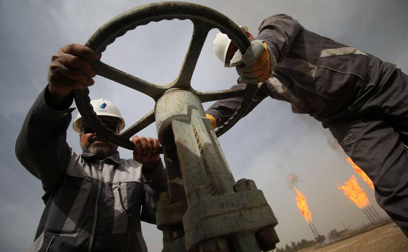 Iraqi oil technicians turn a valve at a gas installation as flames resulting from the burning of excess hydrocarbons rise in the background at the Nahr Bin Omar natural gas field, north of the southern Iraqi port of Basra on January 22, 2018. Iraq will is expected to sign a memorandum of understanding with US energy company Orion on January 22 to tap gas at the oil field in the south of the country, the petroleum ministry said.  The Nahr Bin Omar field, situated in the hydrocarbon-rich Basra province, is currently producing 40,000 barrels of oil a day, but only a small part of the gas from the field is being exploited.  / AFP PHOTO / HAIDAR MOHAMMED ALI