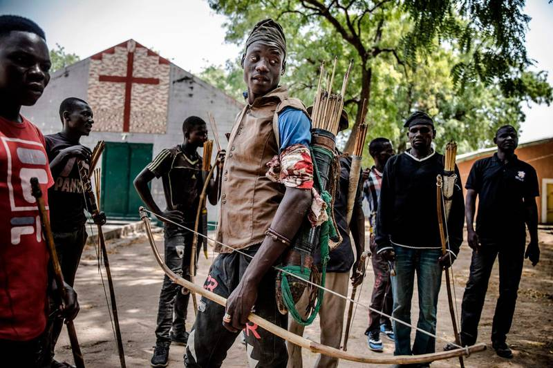 A group of hunters armed with bows and arrows, who fight against herdsmen to protect farmer villages, gather in Dasso, Nigeria on February 18, 2019, just a few days ahead of the country's general election. Nomadic cattle herders and farmers are fighting in near-daily clashes that have left thousands dead in Nigeria and hundreds of villages affected. Both farmers and herdsmen hope the next government would settle their bloody feud. Over the past two years, the fighting has grown more bloody and more politicised with Nigeria's incumbent President being accused of backing herders. / AFP / Luis TATO