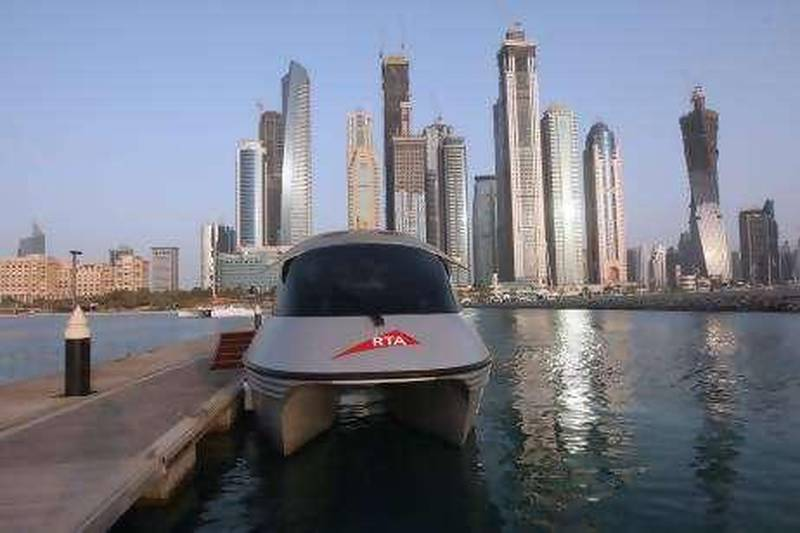DUBAI - JULY 22.2010 - Dubai Water Taxi is park in front of high rise bulidings at Dubai Marina Water Taxi Station.( Paulo Vecina/The National )