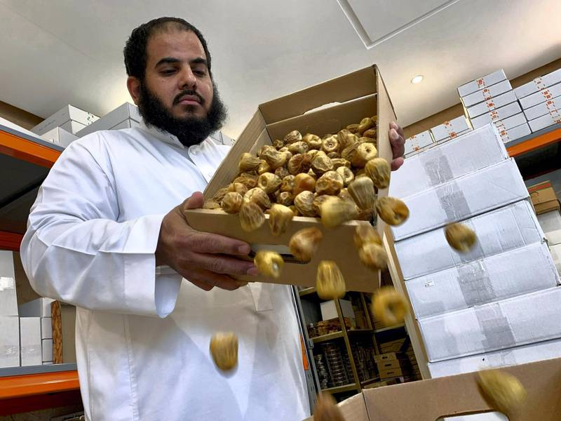A Saudi seller pours dates into a box at his shop, during the 24-hours lockdown to counter the coronavirus disease (COVID-19) outbreak, ahead of the holy fasting month of Ramadan, in Riyadh, Saudi Arabia April 20, 2020. Picture taken April 20, 2020. REUTERS/Nael Shyoukhi