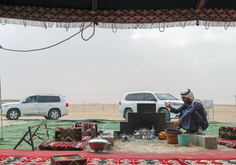 Abu Dhabi, United Arab Emirates, December 11,2019.    -- Hamad Al Merri warms himself by the fireside at his family's tent in the dunes of Al Dhafra.Victor Besa/The NationalSection:  NAReporter:  Anna Zacharias