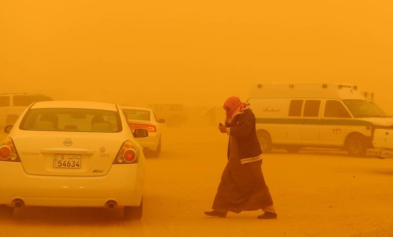 A man walks in the desert camp during a severe dust storm in Rawdatein, 120 Km North of Kuwait City on Saturday, March 17, 2012.  Northwesterly winds of 50 kph carried the dust and sand, to reduce visibility and bring hardship to the desert camp.(AP Photo/Gustavo Ferrari)