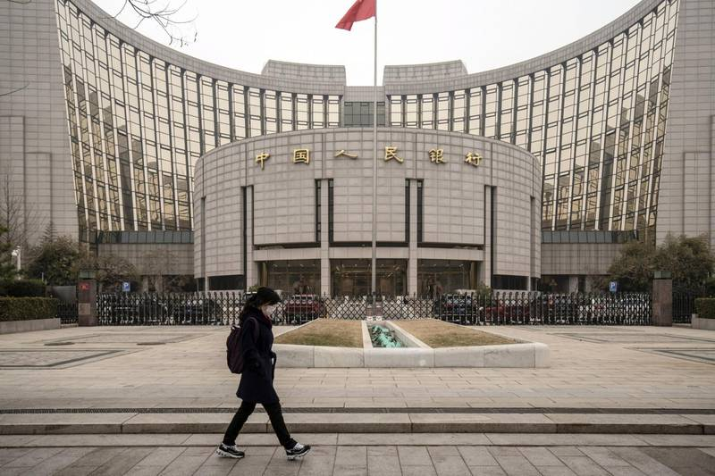 A pedestrian walks past the People's Bank of China (PBOC) building in Beijing, China, on Thursday, March 4, 2021. The low cost of borrowing in China's money markets suggests the central bank again has room to tighten policy by withdrawing liquidity from the financial system -- like it did in January. Photographer: Qilai Shen/Bloomberg