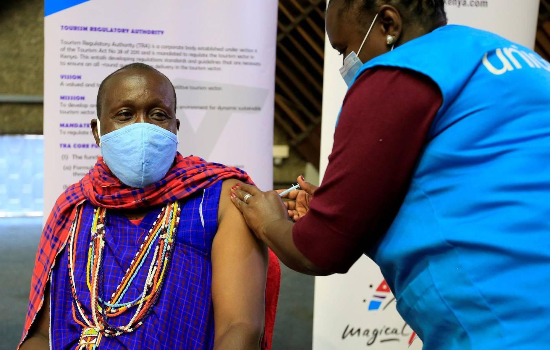 FILE PHOTO: Kenyan tour guide, Daniel Ole Kissipan, receives the AstraZeneca/Oxford vaccine against the coronavirus disease (COVID-19) under the COVAX scheme, in Nairobi, Kenya, April 27, 2021. REUTERS/Monicah Mwangi/File Photo