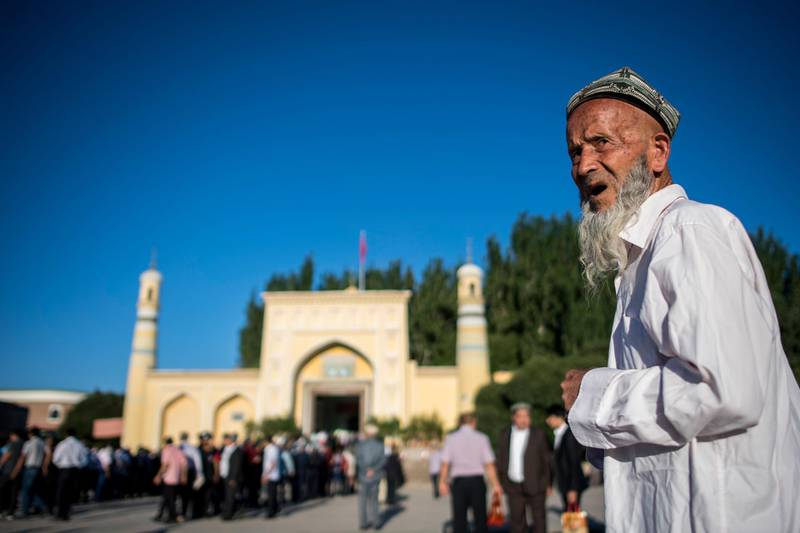 """(FILES) This file picture taken on June 26, 2017 shows a Muslim man arriving in front of the Id Kah Mosque for the morning prayer on Eid al-Fitr in the old town of Kashgar in China's Xinjiang Uighur Autonomus Region.  The prefecture in the region's south has seen an explosion in the construction of """"vocational training"""" centres for the region's Muslim minorities. But the centres have come under international scrutiny, with rights activists describing them as political re-education camps holding as many as one million ethnic Uighurs and other Muslim minorities. - TO GO WITH China-politics-rights-Xinjiang, FOCUS by Ben Dooley  / AFP / Johannes EISELE / TO GO WITH China-politics-rights-Xinjiang, FOCUS by Ben Dooley"""