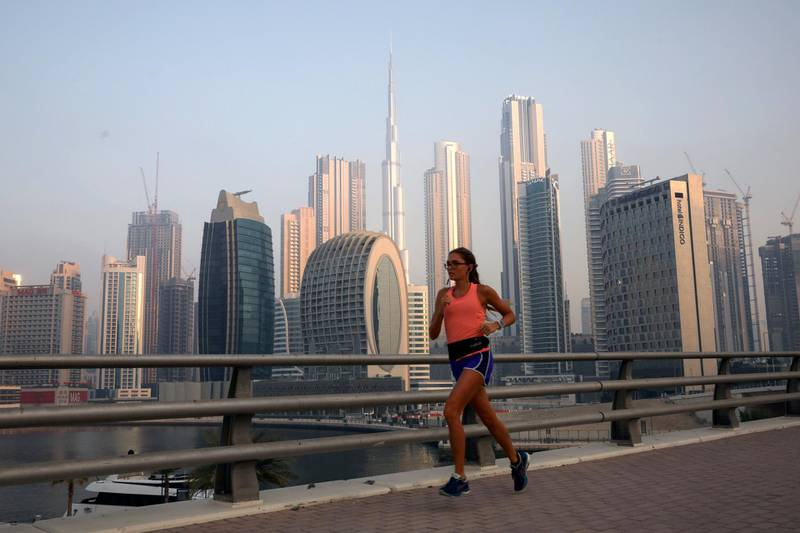 FILE PHOTO: A woman runs past the Burj Khalifa and the downtown skyline in Dubai, United Arab Emirates, June 13, 2021. Picture taken June 13, 2021. REUTERS/Christopher Pike/File Photo