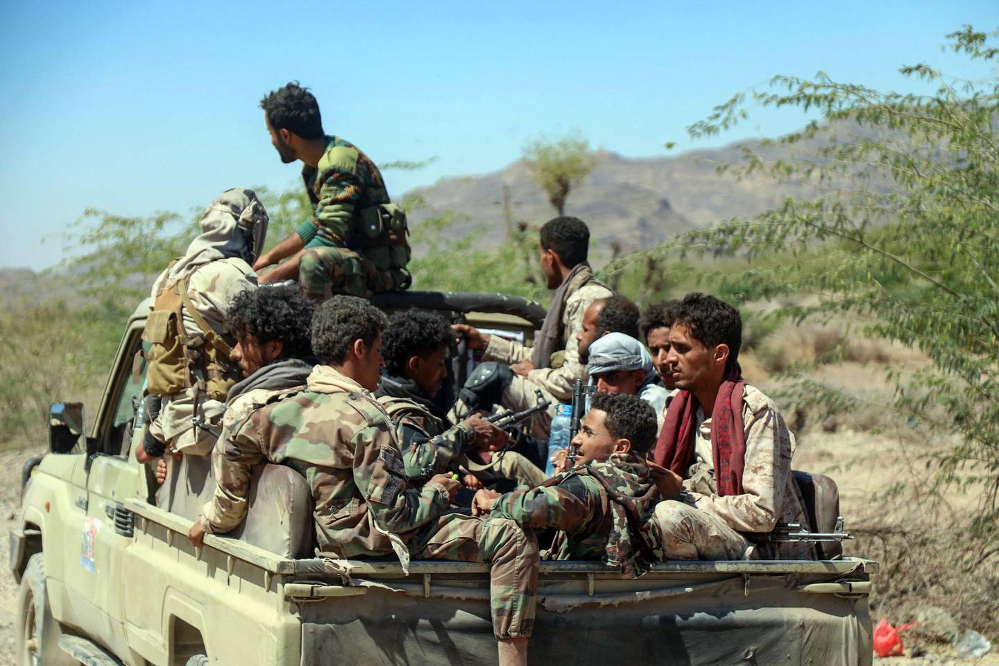 Forces loyal to Yemen's Saudi-backed government sit in the back of a pick-up truck as they deploy during clashes with Huthi rebel fighters west of the country's third-city of Taez, on March 16, 2021. / AFP / Ahmad AL-BASHA