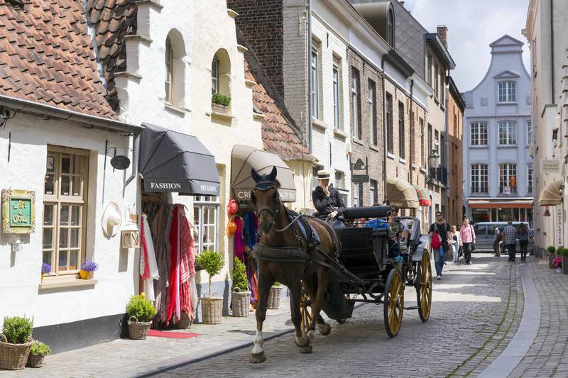 BRUGES, BELGIUM:  Tourists taking traditional horse and carriage sightseeing ride in shopping street in Bruges, Belgium.  (Photo by Tim Graham/Getty Images)