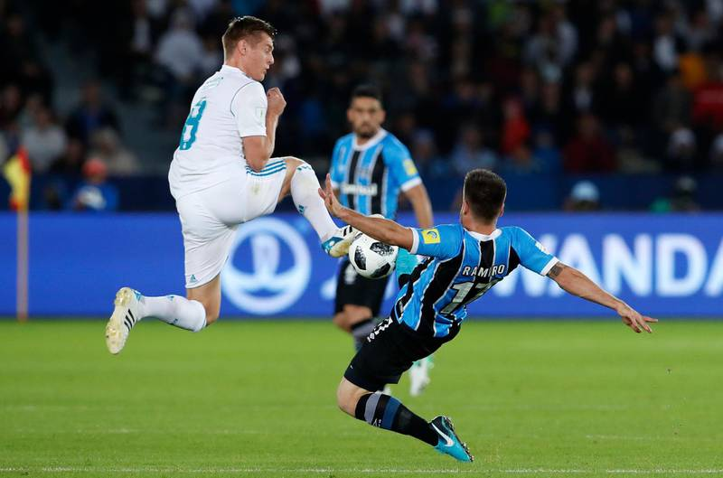 Real Madrid's Toni Kroos, left, goes for the ball with Gremio's Ramiro during the Club World Cup final soccer match between Real Madrid and Gremio at Zayed Sports City stadium in Abu Dhabi, United Arab Emirates, Saturday, Dec. 16, 2017. (AP Photo/Hassan Ammar)
