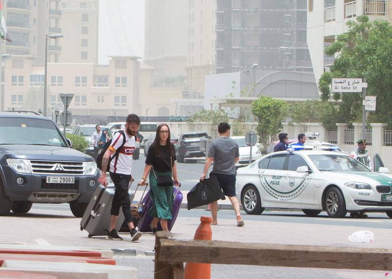 DUBAI, UNITED ARAB EMIRATES 13 MAY 2018 - Tourists in one of the hotels in Marina  with their luggage to find a cab  as police block the area around the burning building. Leslie Pableo for The National