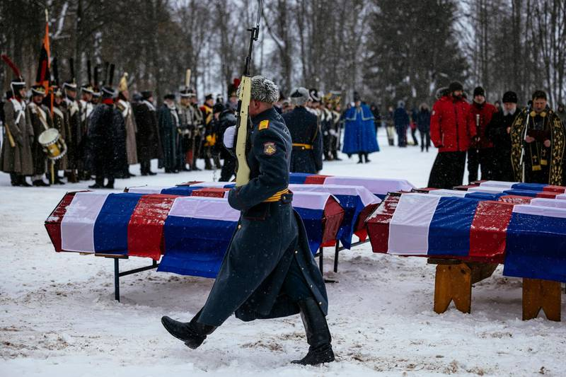 A Russian honour guard passes by coffins containing remains of Russian and French soldiers during a burial ceremony in the western town of Vyazma on February 13, 2021. Officials and descendants of 19th-century Russian and French military leaders gathered for a windswept ceremony in the western town of Vyazma to re-bury the remains of 126 people killed in one of the bloodiest battles of Napoleon's Russian campaign. / AFP / Dimitar DILKOFF