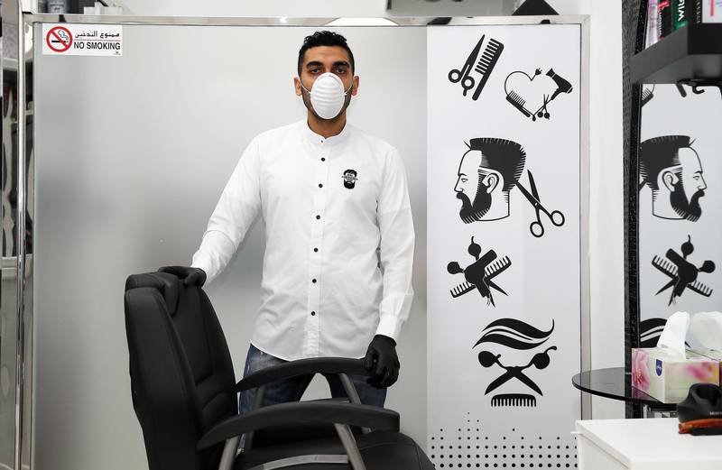 DUBAI, UNITED ARAB EMIRATES , March 25 – 2020 :- Taha Hussein, 34 years old from Egypt working as a hairdresser at the Hair & Beard gents salon near the Mövenpick Ibn Battuta Gate Hotel in Dubai. He is married and has two daughters. He told as a safety measure in these circumstances whenever someone is coming to the salon they are using disposable capes and blades for their customers. There is a sanitizer placed at the cash counter for the customers as a preventive measure against coronavirus in Dubai. He is using facemask, gloves, washing and sanitizing his hands regularly for his safety. He said customer appreciate his services in these circumstances.  (Pawan Singh / The National) For Unsung Hero of UAE Photo Feature