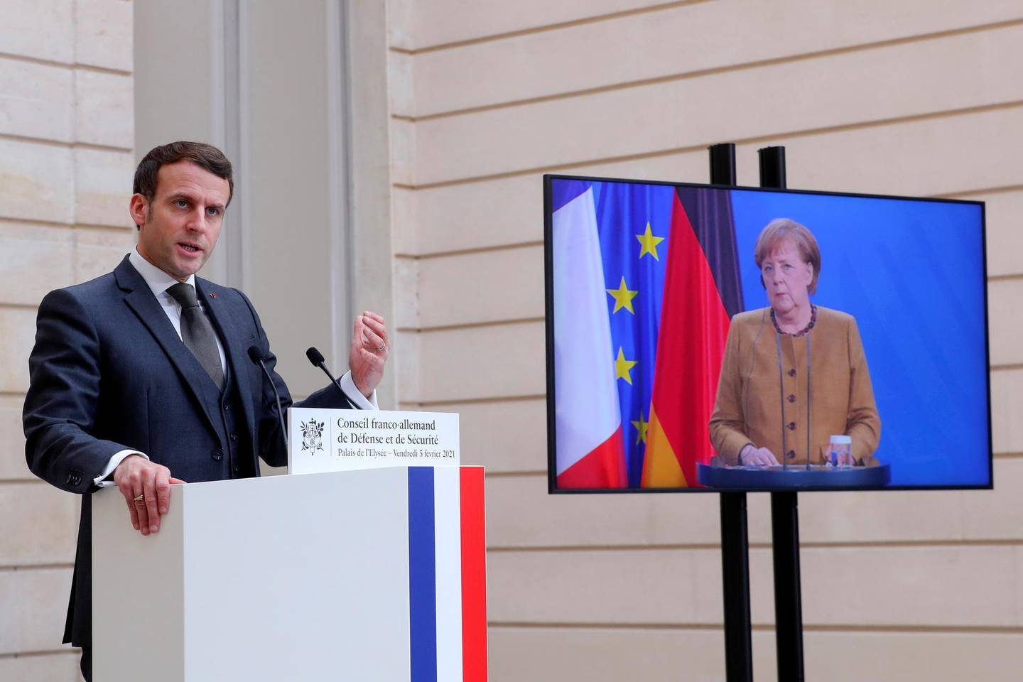 French President Emmanuel Macron speaks as German Chancellor Angela Merkel looks on after a German-French Security Council video conference at the Elysee Palace in Paris, France February 5, 2021.   Thibault Camus/Pool via REUTERS