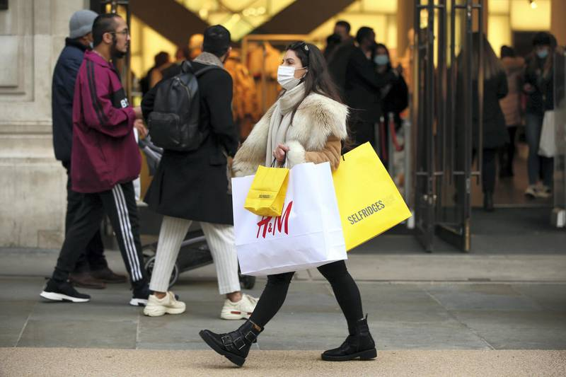 A woman wearing a face mask carries bags of shopping from clothing retailer HM and department store Selfridges along Regent Street in London, England, on December 5, 2020. London has returned to so-called Tier 2 or 'high alert' coronavirus restrictions since the end of the four-week, England-wide lockdown last Wednesday, meaning a reopening of non-essential shops and hospitality businesses as the festive season gets underway. Rules under all three of England's tiers have been strengthened from before the November lockdown, however, with pubs and restaurants most severely impacted. In London's West End, meanwhile, Oxford Street and Regent Street were both packed with Christmas shoppers this afternoon, with the retail sector hoping for a strong end to one of its most difficult years. (Photo by David Cliff/NurPhoto via Getty Images)