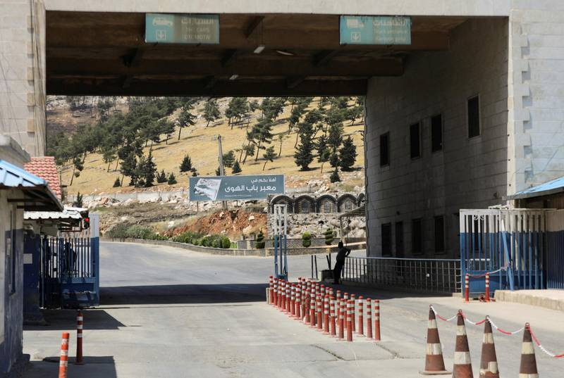 """A road sign that reads """"Welcome to Bab al-Hawa crossing"""" is seen at Bab al-Hawa crossing at the Syrian-Turkish border, in Idlib governorate, Syria June 10, 2021. Picture taken June 10, 2021. REUTERS/Khalil Ashawi"""